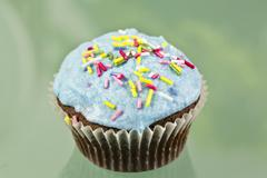 A chocolate cupcake decorated with blue buttercream icing and sugar strands Stock Photos