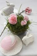 An idea for an Easter decoration: a porcelain hare, and paper pinks in a nest Stock Photos