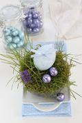 An egg decorated with a ribbon and chocolate eggs in an Easter nest made of moss Stock Photos