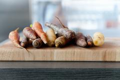Carrots of assorted colours on a chopping board Stock Photos