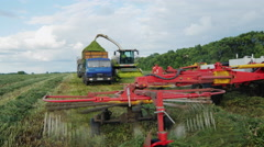 Agricultural machinery to harvest. Harvester collects grass in a heap, the other Stock Footage