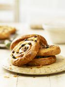 Raisin whirls on a wooden plate Stock Photos