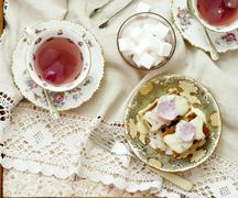 Almond cakes topped with rose petals and sugar icing, with rose tea and sugar Stock Photos