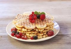 Waffles with raspberries, blueberries and redcurrants on a wooden plate Stock Photos