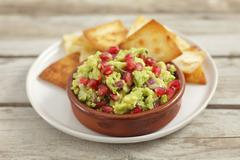 Guacamole with pomegranate seeds and tortilla chips Stock Photos