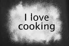 I love cooking' etched in icing sugar on a black background Stock Photos
