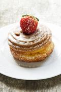 Yeast-raised pastry whirl with sugar glaze and a strawberry Stock Photos