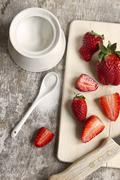 Strawberries on a chopping board; scattered sugar to one side Stock Photos