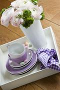 A bunch of spring flowers in a vase alongside a stack of side plates and coffee Stock Photos