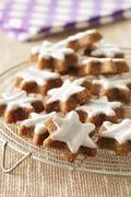 Star-shaped cinnamon biscuits on a cooling rack Stock Photos
