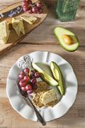 Gluten Free Crackers with Garlic and Herb Cheddar Cheese, Avocado and Red Grapes Stock Photos