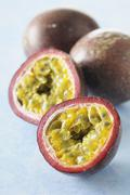 Purple passion fruits, whole and halved Stock Photos