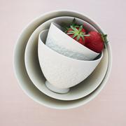 Two strawberries in white, overturned ceramic bowls Stock Photos