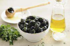 Black olives in a bowl with parsley and olive oil Stock Photos