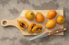 Medlars, whole and halved, on a chopping board Stock Photos