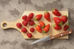 Fresh strawberries and raspberries on a chopping board with a knife Stock Photos