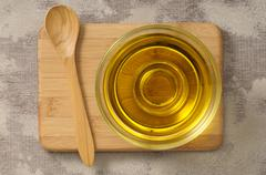 Olive oil in a glass dish on a chopping board with a wooden spoon Stock Photos