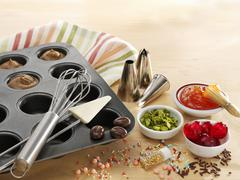 A muffin tray with batter, baking utensils and toppings Stock Photos