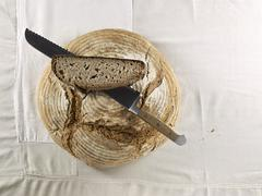 A brown loaf, with a bread knife and a slice of bread lying on top of it Stock Photos