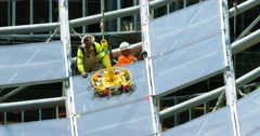 Construction workers install glass windows at development site 4K RAW Stock Footage