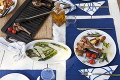 Grilled lamb chops with green asparagus, cherry tomatoes and roast potatoes on a Kuvituskuvat