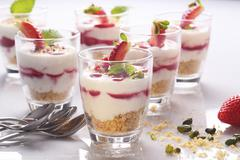 Layered strawberry dessert with pistachios and a crumb base Stock Photos