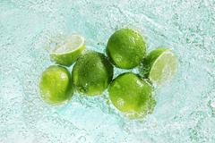 Limes in sparkling water Stock Photos