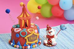 A party cake designed as a circus tent and a fondant bear with a cake pop Stock Photos