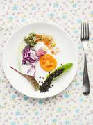 A salad plate with tomato, red cabbage, edible shoots and black lentils Stock Photos