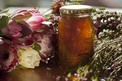 A jar of honey with honeycomb, surrounded by flowers Stock Photos
