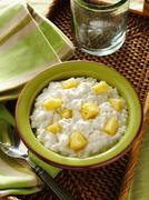 Small curd cottage cheese with pineapple chunks in green bowl on a woven tray Stock Photos