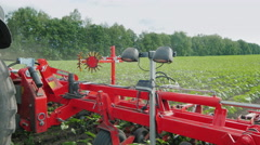Steadicam shot: Agricultural machinery for weeding fields. His tractor pulls Stock Footage