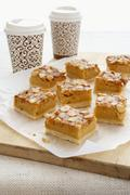 Macadamia nut slices with coffee in takeaway cups Stock Photos