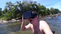 Man in tropical lagoon with VR virtual headset dives under Stock Footage