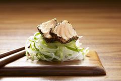 Seared peppered salmon on a bed of daikon and cucumber ribbons Stock Photos