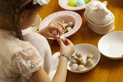 A girl peeling quail's eggs Stock Photos