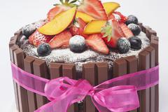 Chocolate torte with fresh fruit, icing sugar and a pink ribbon Stock Photos