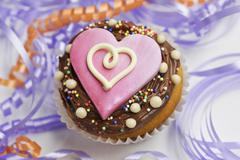 A cupcake decorated with chocolate icing and a pink heart between streamers Stock Photos