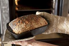 Hands holding a loaf tin with freshly baked wholemeal bread Stock Photos