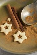 Star-shaped biscuits, ground cinnamon, cinnamon sticks and a spoon Stock Photos