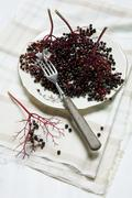 Lots of elderberries, in bunches and individually, on an old plate with a fork Stock Photos
