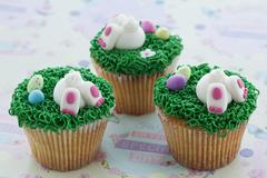 Vanilla cupcakes with buttercream and sweet Easter-themed decorations Stock Photos