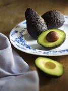 Whole and halved avocado Stock Photos