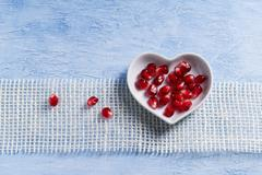 Pomegranate seeds in a heart-shaped bowl Stock Photos