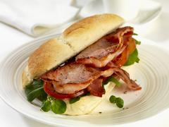 A bread roll filled with bacon, tomatoes, rocket and watercress Stock Photos