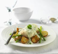 Cod in parsley sauce with fried potatoes and asparagus Stock Photos
