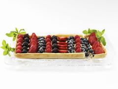 A Rectangular Mixed Berry Fruit Tart on a Glass Tray Garnished with Mint Leaves Stock Photos