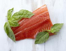 A Fresh Filet of Salmon with Fresh Basil Leaves Stock Photos