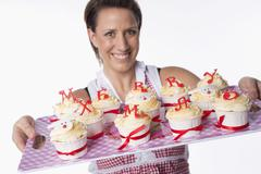 A woman holding a tray of cupcakes topped with letters reading 'Merry Xmas' Stock Photos