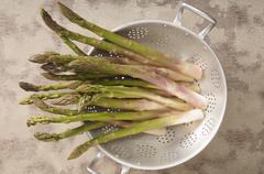 Green asparagus in a colander Stock Photos